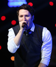Picture of Adam Young singing at a concert